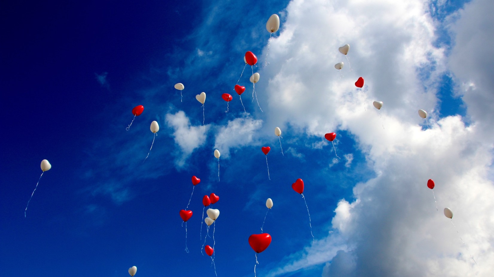 Red and white heart balloons in the sky