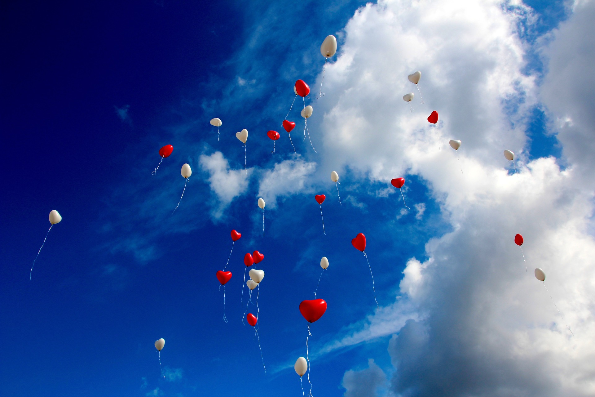Red and white heart balloons floating into the sky